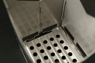 Le fond du réchaud, percé de trou permettant à la cendre de tomber et facilitant la combustion
